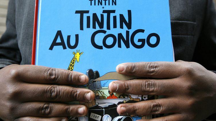 "Bienvenu Mbutu Mondondo tient un album de ""Tintin au Congo"", le 7 août 2007, à Bruxelles (Belgique). (SEBASTIEN PIRLET / BELGA MAG / BELGA / AFP)"