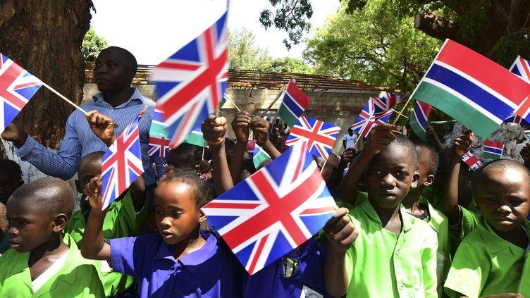Ces enfants agitent des drapeaux britanniques et gambiens en attendant l'arrivée de la duchesse Camilla et du prince de Galles qui ont atterri la veille en Gambie. C'est ce pays que Charles a choisi pour sonpremier déplacement depuis qu'il dirige le Commonwealth. La tournée africaine de 11 jours du couple princier a pour objectif de «célébrer le partenariat dynamique et tourné vers l'avenir du Royaume-Uni avec ces pays du Commonwealth», ont indiqué les services du prince dans un communiqué. (SEYLLOU / POOL / AFP)