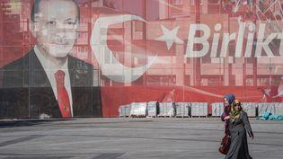 Deux femmes marchent devant une grande affiche dans la rue montrant le président turc Recep Tayyip Erdogan à Konya, en Turquie, le 27 octobre 2018 (illustration). (DIEGO CUPOLO / NURPHOTO / AFP)