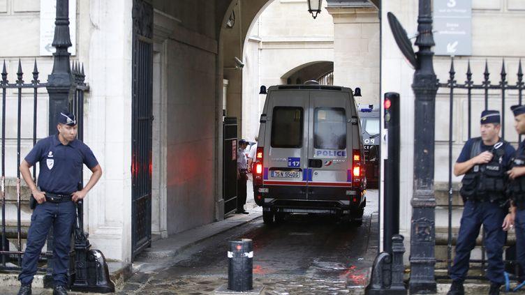 Un fourgon de la police arrive au siège de la police judiciaire, le 6 août 2014, avec à bord l'un des deux officiers de police mis en cause dans l'affaire de vol de cocaïne. (KENZO TRIBOUILLARD / AFP)