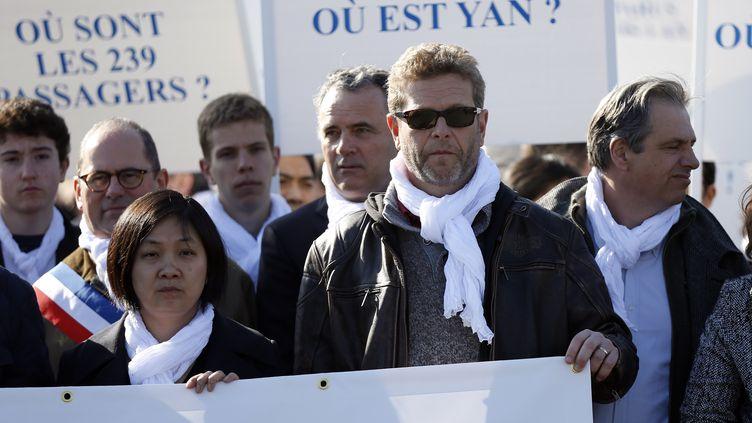 Ghyslain Wattrelos (avec les lunettes de soleil) participe à une marche silencieuse à Paris, à l'occasion du premier anniversaire de la disparition du vol MH370 de Malaysia Airlines, le 8 mars 2015. (THOMAS SAMSON / AFP)