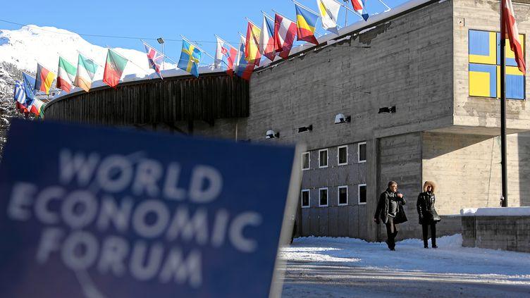 Des passants circulent devant le Centre des congrès de Davos (Suisse), la veille de l'ouverture de la 44e édition du Forum économique mondial, mardi 21 janvier 2014. ((NOTIMEX / AFP))