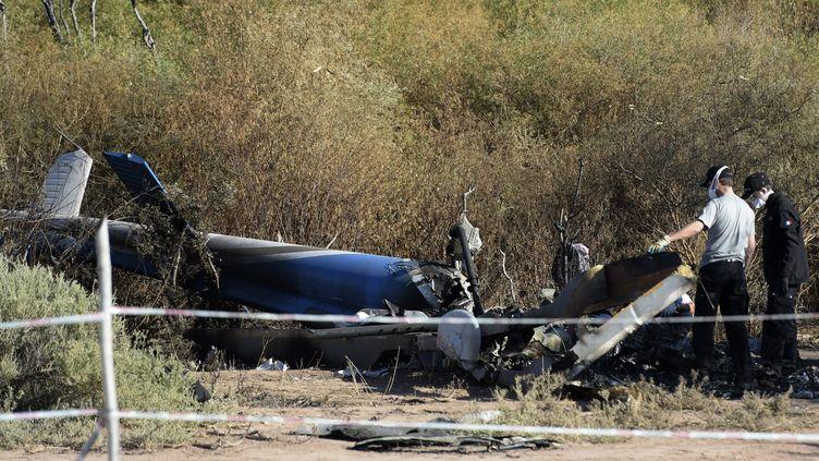 Des enquêteurs inspectent la carcasse d'un des deux hélicoptères impliqués dans l'accident, le 12 mars 2015 à Villa castelli (Argentine). (JUAN MABROMATA / AFP)