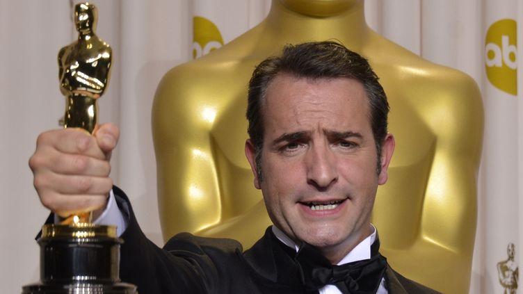 Jean Dujardin brandit son Oscar de meilleur acteur pour sa performance dans The Artist, le 26 février 2012 à Los Angeles (Etats-Unis). (JOE KLAMAR / AFP)