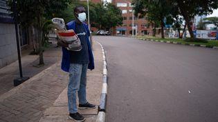 Un vendeur de journaux, dans les rues désertées de Kigali, soumises aux mesures de confinement face à la pandémie de coronavirus, le 22 mars 2020. (SIMON WOHLFAHRT / AFP)