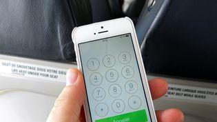 Un passager utilise son smartphone dans un avion, le 12 mars 2014 à l'aéroport de Rome Fumicino. (  MAXPPP)
