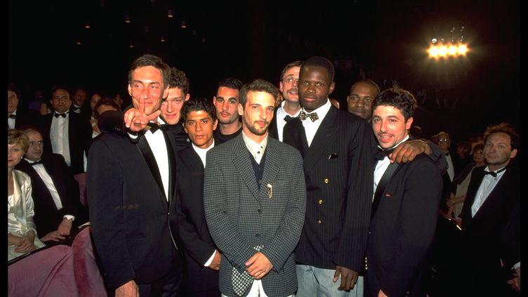 """Une partie de l'équipe de """"La Haine"""" lors de la projection au Festival de Cannes le 27 mai 1995. De gauche à droite : François Levantal, Vincent Cassel, Saïd Taghmaoui, Mathieu Kassovitz, Christophe Rossignon, Hubert Koundé et Marc Duret. (ERIC ROBERT / SYGMA / GETTY IMAGES)"""