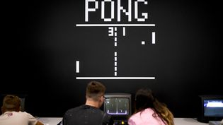Des joueurs devant le jeu vidéo Pong, créé en 1972.A Cologne en 2019. (INA FASSBENDER / AFP)
