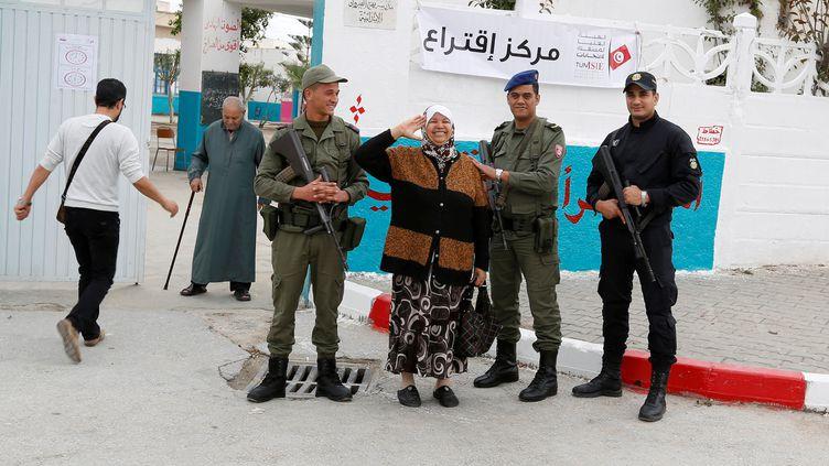 Une Tunisienne pose en compagnie de soldats et d'un policier devant un bureau de vote à Tunis (pour les municipales le 6 mai 2018). (REUTERS - ZOUBEIR SOUISSI / X02856)