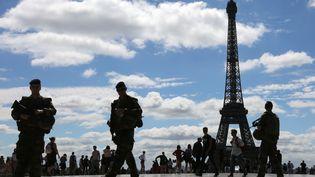 Des militaires de l'opération Sentinellepatrouillent devant la Tour Eiffel, à Paris, le 25 juin 2017. (LUDOVIC MARIN / AFP)