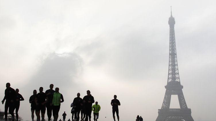 Des joggeurs courent sur l'esplanade du Trocadéro en plein pic de pollution aux particules fines, à Paris, le 11 mars 2014. (LUDOVIC MARIN / AFP)