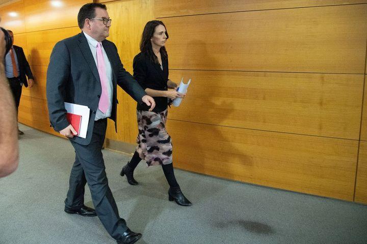 La Première ministre néo-zélandaise Jacinda Ardern et le ministre des Finances Grant Robertson arrivent pour participer à une conférence de presse un jour avant que le pays ne soit mis en quarantaine, au Parlement de Wellington le 24 mars 2020. (MARTY MELVILLE / AFP)