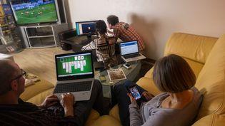 Une famille passe du temps devant différents écrans. (MAXPPP)