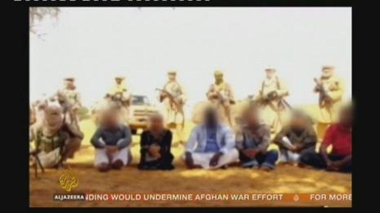 Sur la photo, les sept otages, dont cinq Français, sont assis devant leurs ravisseurs en armes (Al -Jazira)