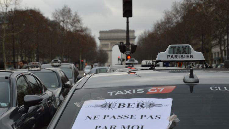 Une pancarte hostile àUber sur la vitre arrière d'un taxi, à Paris, le 26 janvier 2016. (CITIZENSIDE / AFP)