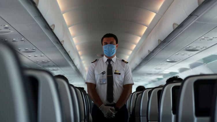 Un membre d'équipage porte un masque à bord d'un avion d'une compagnie égyptienne le 18 juin 2020. La grande majorité des personnels navigants sont en chômage technique. (MOHAMED ABD EL GHANY / X02738)