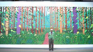 "David Hockney devant sa toile David Hockney devant sa toile ""The Arrival of spring in Woldgate, East Yorkshire"" offerte au Centre Pompidou Paris  (STEPHANE DE SAKUTIN / AFP)"