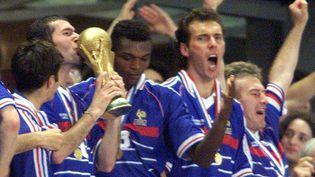 Zinédine Zidane embrasse la coupe du monde, au Stade de France, le 12 juillet 1998. (GRIGORY DUKOR / REUTERS)