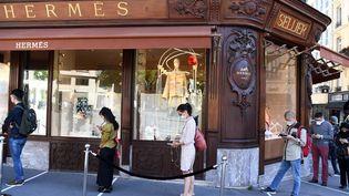 Des clients respectent les distances sociales devant le magasin Hermes situé sur l'avenueGeorge V, à Paris, le 20 mai 2020, (ALAIN JOCARD / AFP)