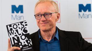 """David Grossman tient un exemplaire de son roman """"Un cheval entre dans un bar"""", lauréat du Man Booker International Prize, le 13 juin 2017 à Londres  (Ray Tang / Anadolou Agency / AFP)"""