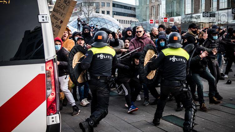 Des manifestants face à la police anti-émeute, le 24 janvier 2021, àEindhoven, aux Pays-Bas. (ROB ENGELAAR / ANP / AFP)