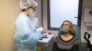 Une infirmière réalise un test PCR sur une patiente, près de Lille (Nord), le 22 décembre 2020. (JEANNE FOURNEAU / HANS LUCAS)