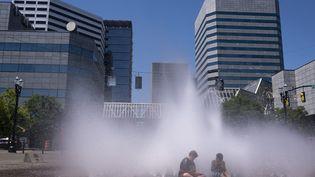 Des enfants dans une fontaine de Portland (Etats-Unis) pour échapper à la chaleur, le 27 juin 2021. (NATHAN HOWARD / GETTY IMAGES NORTH AMERICA / AFP)