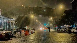 Un passant traverse une rue du Bronx balayée par des trombes d'eau, le 1er septembre 2021 à New York (Etats-Unis). (DAVID DEE DELGADO / GETTY IMAGES NORTH AMERICA / AFP)