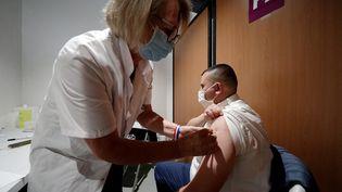 Une soignante administre une dose de vaccin à un patient à Poissy (Yvelines), le 23 juin 2021. (GEOFFROY VAN DER HASSELT / AFP)