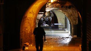 Des policiers israéliens près du corps de l'assaillant palestinien abattu samedi 3 octobre, à Jérusalem. (AHMAD GHARABLI / AFP)