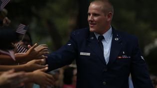 Spencer Stone salue la foule lors d'une parade à Sacramento (Californie, Etats-Unis), le 11 septembre 2015. (STEPHEN LAM / GETTY IMAGES NORTH AMERICA / AFP)