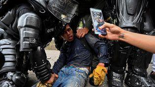 Des policiers colombiens arrêtent un manifestant lors d'une manifestation contre le gouvernement à Cali (Colombie), le 10 mai 2021.  (LUIS ROBAYO / AFP)
