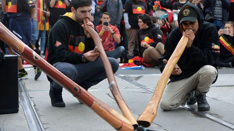 instrument traditionnel aborigène, participent à la semaine de NAIDOC (National Aboriginal and Islander Day Observance Committee - Comité d'Observance des Aborigènes et Insulaires), ici à Melbourne. Les Aborigènes australiens sont les premiers occupants de l'île-continent, les «insulaires» sont, quant à eux, les habitants initiaux des îles du détroit de Torrès (l'archipel se trouvant entre l'Australie et la Nouvelle-Guinée Papouasie).  Après avoir tenté, et presque réussi, à faire disparaître ces populations autochtones par absorption biologique (couper les enfants de leurs parents et les placer, loin, dans des familles blanches), l'Australie les met maintenant à l'honneur, leur rend hommage et reconnaît la qualité et la pertinence de leurs différents savoirs ancestraux.   La thématique de la cuvée 2016 est « Le temps des rêves », ce chant qui désigne l'ère qui précède la création de la Terre dans les croyances anciennes aborigènes.   Le Ministre de la Police, Bill Byrne a expliqué son opinion sur cette semaine, « qui se déroule du 3 juillet au 10 juillet qui est un moment important qui permet d'embrasser et de célébrer la culture et les accomplissements des premiers australiens ».   (Recep Sakar / Anadolu Agency)