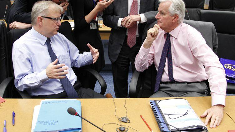Le commissaire européen à l'Economie et aux Affaires monétaires, Olli Rehn (à gauche), et le commissaire européen au Marché interne, Michel Barnier, le 4 octobre 2011 au Luxembourg. (FRANÇOIS LENOIR / REUTERS)