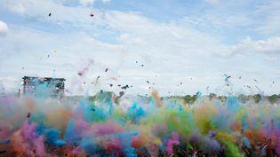 Des festivaliers lancent de la poudre colorée lors de la 21e édition des Solidays, le 23 juin 2019. (AFP)