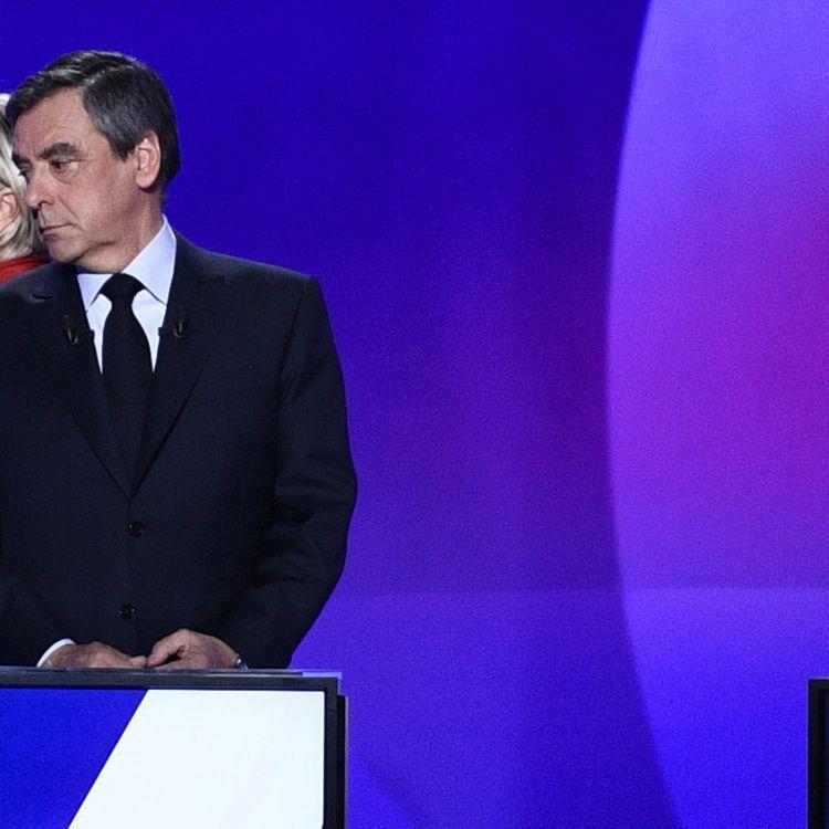 """La candidate du Front national, Marine Le Pen, passe derrière son rival desRépublicains, le 20 avril 2017, lors de l'émission """"15 minutes pour convaincre"""" sur France 2. (MARTIN BUREAU / AFP)"""