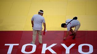 Des juges vérifient le tatami, le 21 juillet 2021, à Tokyo (Japon). (FRANCK FIFE / AFP)
