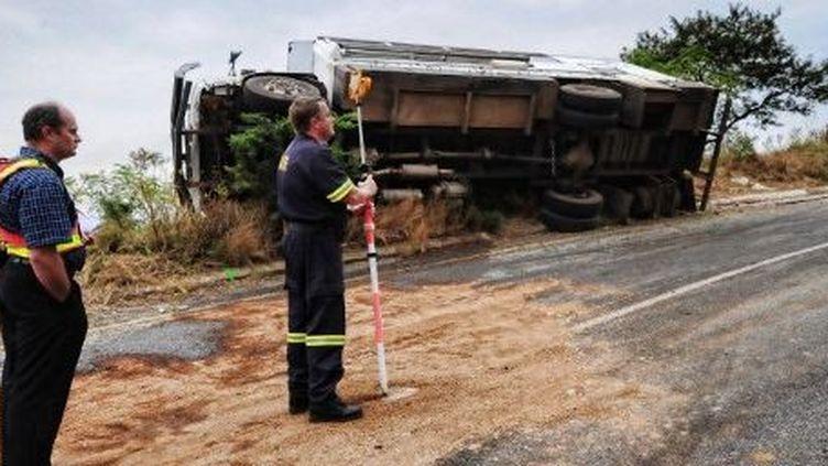 Des policiers sud-africains inspectent les lieux d'un accident de car ayant fait deux morts et 18 blessés, le 10 janvier 2010 près de Nelspruit.  (AFP PHOTO / Martin BERNETTI)