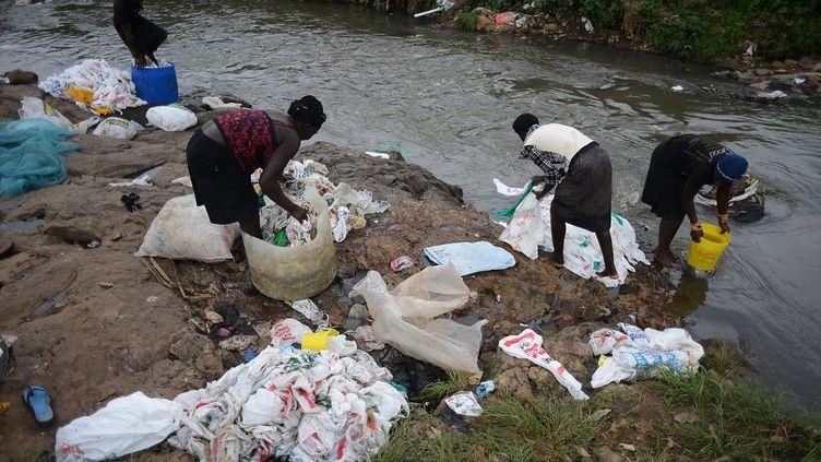 A Nairobi, au Kenya, des femmes lavent des sacs en plastique afin de les réutiliser. Depuis 2018, la vente des sacs en plastique est interdite dans le pays. (SIMON MAINA / AFP)