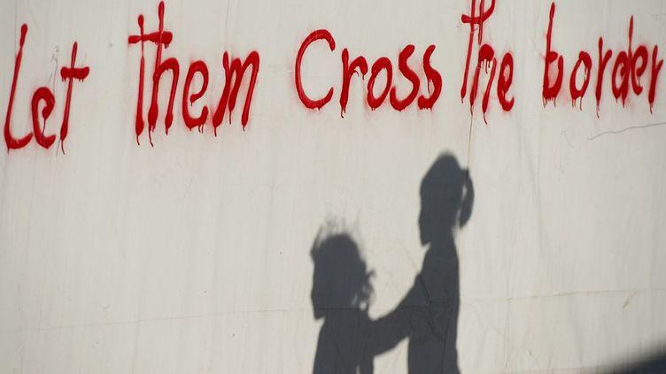 ...surplombée du tag rageur «Let them cross the border» (Laissez-les traverser la frontière) sur un mur d'Idoméni en Grèce. 54.000 personnes sont coincées à différents endroits de la Grèce etdes Balkansdu fait de la fermeture en cascade des frontières de ces pays depuis février 2016.10.000 d'entre elles se trouvent à Idoméni, la frontière gréco-macédonienne non loin de là étant hermétiquement fermée par les autorités macédoniennes, comme celles de leurs voisins. Les conditions de vie à Idoméni sont exécrables, estiment les organisations de défense des droits de l'Homme. Il est urgent pour les réfugiés d'en partir. (TOBIAS SCHWARZ / AFP)