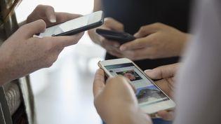 Utilisateurs de téléphones mobiles. (HERO IMAGES VIA GETTY IMAGES)