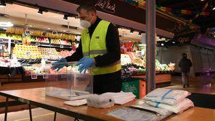 Mise en place d'un point de vote pour les élections régionales en Catalogne à Barcelone, dans le marché de Ninot, le 10 février 2021. (LLUIS GENE / AFP)