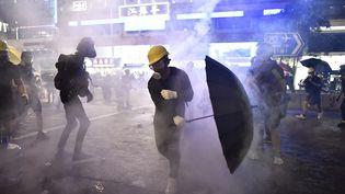 Des manifestants pro-démocratie au milieu des gaz lacrymogènes, le 28 juillet 2019, à Hong Kong. (ANTHONY WALLACE / AFP)