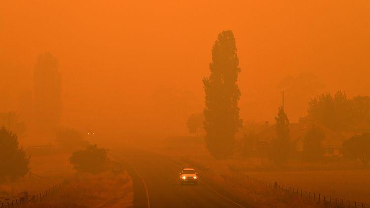 Une route enNouvelle-Galles du Sud sous un nuage de fumée orangé à cause des incendies qui ravagent le pays, le 5 janvier 2020.  (SAEED KHAN / AFP)