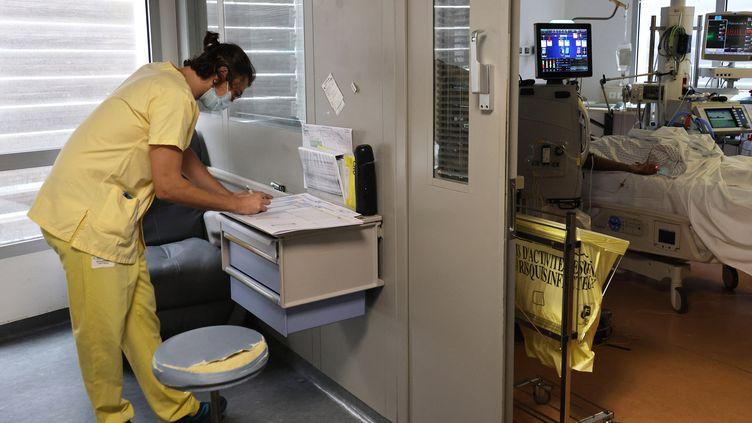 Un soignant remplit des documents près de la chambre d'un patient atteint du Covid-19 dans le service de réanimation de l'hôpital de Saint-Pierreà La Réunion, le 30 juillet 2021. (RICHARD BOUHET / AFP)