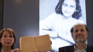 Teresien da Silva (à gauche) et Ronald Leopold, de la fondation Anne Frank, dévoilent les deux pages inédites du journal de l'adolescente. (PETER DEJONG / SIPA / AP)