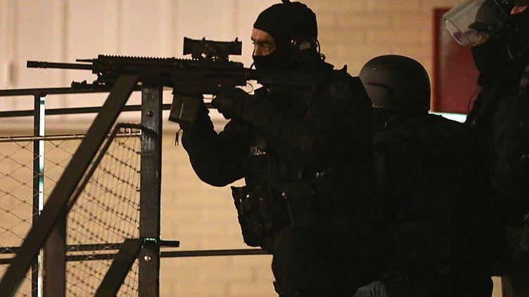 """Un policier, lors d'une opération à Reims, dans le quartier de laCroix-Rouge, dans la nuit du 7 au 8 janvier 2015, lors de la traque des auteurs de l'attentat contre """"Charlie Hebdo"""". (FRANCOIS NASCIMBENI / AFP)"""