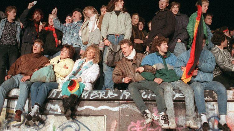 De jeunes Allemands assis sur le mur de Berlin, le 10 novembre 1989. (PETER KNEFFEL / NULL)