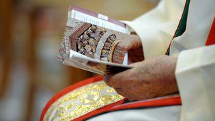 Dans la cathédrale de Saint-Dié, un prêtre tient un livre de messe. Il assiste à la bénédiction del'huile qui servira aux baptêmes de Pâques, le 15 avril 2014. (MAXPPP)