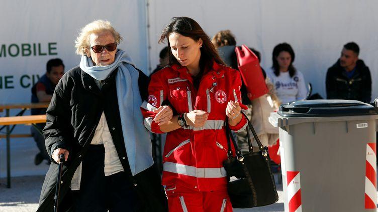 Une habitante de Norcia (Italie), prise en charge par une membre de la Croix-Rouge italienne, le 30 octobre 2016. (REMO CASILLI / REUTERS)